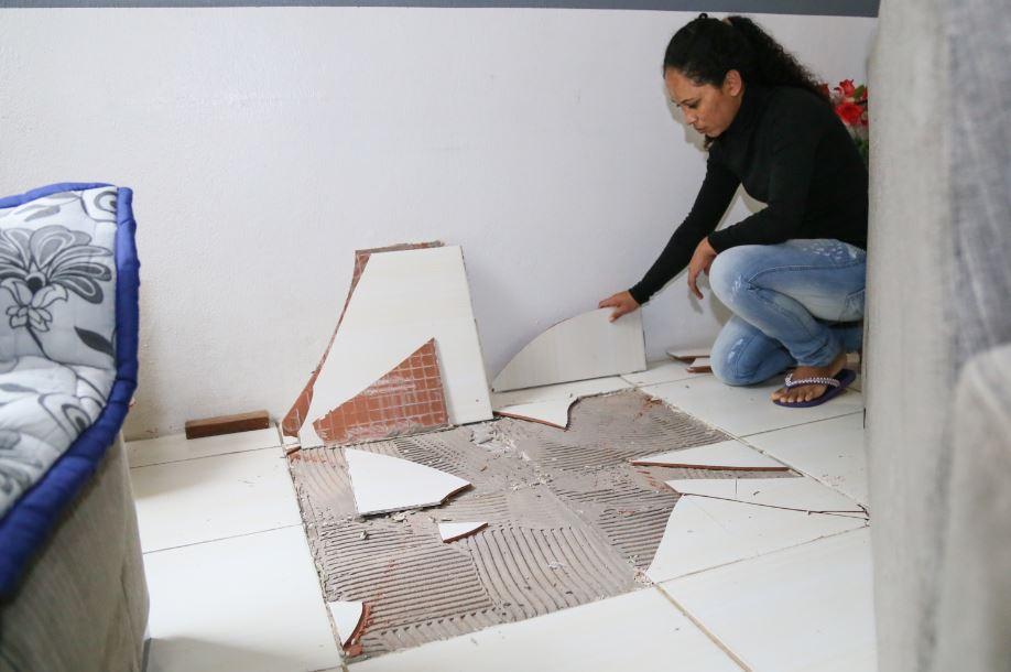 Nilvania mostra o estrago causado no piso do apartamento em que mora com os três fihos | Foto: Eduardo Montecino/OCP