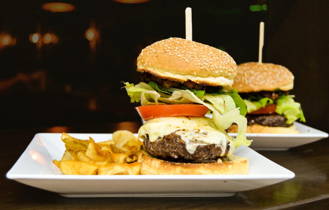 Hambúrguer da casa (queijo mussarela, queijo gorgonzola, cebolas grelhadas, bacon, salada e pão com gergelim). | Foto: Divulgação.